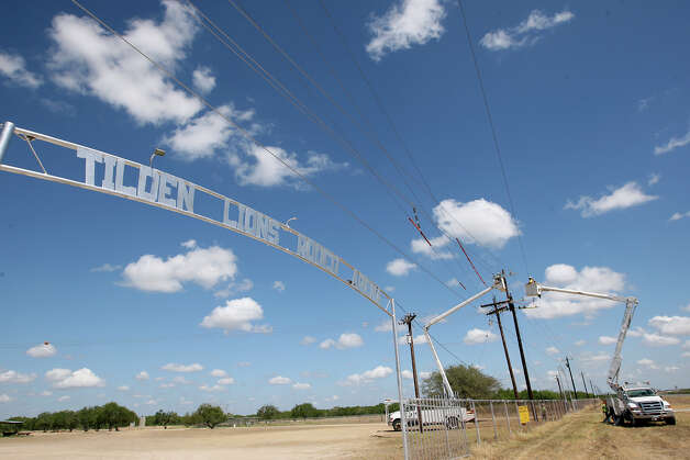 Power line construction workers reconstruct power lines in Tilden, Texas, Thursday, August 9, 2012. The reconstruction is to accommodate demand for power from the oil and gas activity in the area. The 7,200-volt power lines are being replaced by 14,400-volt lines. Photo: Jerry Lara, San Antonio Express-News / © 2012 San Antonio Express-News