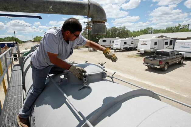 "Water hauler Oscar Garza prepares to load up at the McMullen County Water Control and Improvement District 1 in Tilden, Texas, Thursday, August 9, 2012. According to the district manager Alan Brown, they sell between 50,000 to 75,000 gallons a day to oilfield related companies. Before the oil boom, the district would sell around 10,000 gallons a day. It was run on the honor system with the pump left opened all day. ""People would come fill up then go to Joe's (Joe's Food Market) and pay,"" Brown recalled. In the near future, a computerize system will be in place. Demand for water has increased as companies opened field offices and locals open RV Parks. An 80-unit apartment complex along with 12-unit industrial yard and 25-40 home sites was proposed on land across the Frio River from Tilden. The parcel was out of the water district. ""Looking at the numbers, we're not going to furnish the kind of water they would have to have for that location,"" said Brown. The well has a capacity of 275,000 gallons a day. Some months, especially during the summer, daily averages reach 225,000 gallons. Photo: Jerry Lara, San Antonio Express-News / © 2012 San Antonio Express-News"
