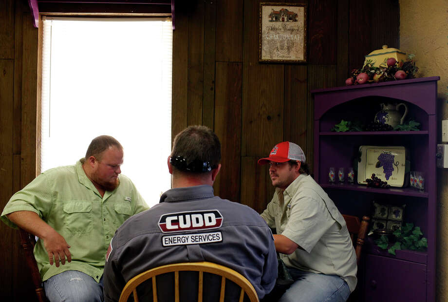 "Chad Gilbert, left, and Mike Morrison, right, workers at K & C Hose and Supply, an oil field supply store, eat lunch with a friend who works in the oil industry at Cactus Garden in Pleasanton on Wednesday, August 8, 2012. ""It's a win, win for everybody in the community,"" Cactus Garden restaurant owner Nikki Mitchell says. Mitchell says her  business has increased by ""leaps and bounds."" Photo: Lisa Krantz, San Antonio Express-News / San Antonio Express-News"