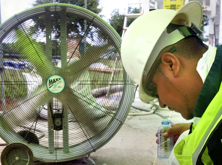 A worker seeks relief in front of a fan while making repairs outdoors during one of Houston's hot spells (Chronicle file photo). Photo: Cody Duty, Houston Chronicle / © 2011 Houston Chronicle