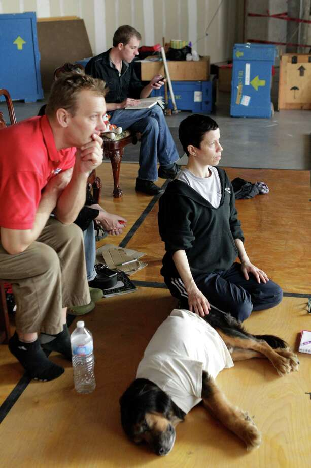 """David Graeve, installation artist, left, Jane Weiner, Hope Stone Dance Company artistic director, right, with dog named Oliver Jones, and Jeremy Choate, lighting designer, back center, watch during rehearsal for la vie a pleines dents which means """"to bite life with all of one's teeth"""" for a pop-up theater at the Houston Pavilions, 1201 Fannin, Thursday, Jan. 5, 2012, in Houston. ( Melissa Phillip / Houston Chronicle ) Photo: Melissa Phillip / © 2011 Houston Chronicle"""