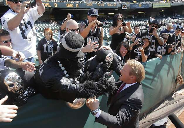 Ex-coach Jon Gruden gets a warm reception from the fans and other creatures in the Black Hole. Photo: Carlos Avila Gonzalez, The Chronicle