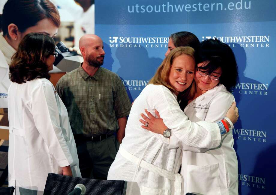 Carrie Jones, second from right, hugs Dr. Julie Lo following a news conference in Dallas on Monday just days after Jones gave birth to quintuplets. For Jones and husband Gavin, center, the newborns add more children to what was once a single-child household. Photo: Brad Loper / The Dallas Morning News