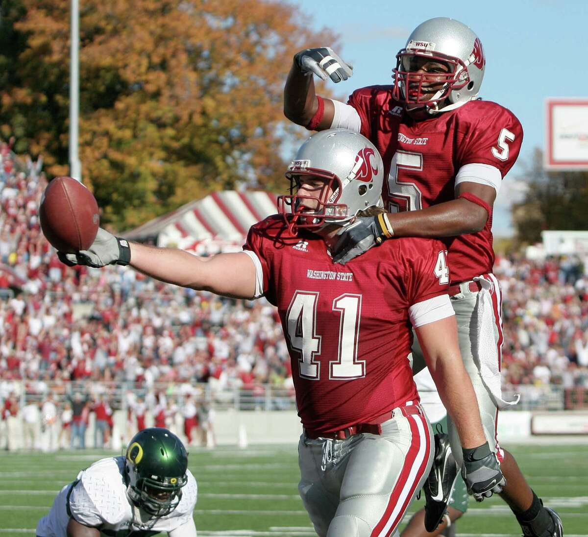 Tight end Jed Collins #41 of the Washington State Cougars celebrates with Michael Bumbus #5 after scoring a touchdown in the first half against the Oregon Ducks on October 21, 2006 at Martin Stadium in Pullman.