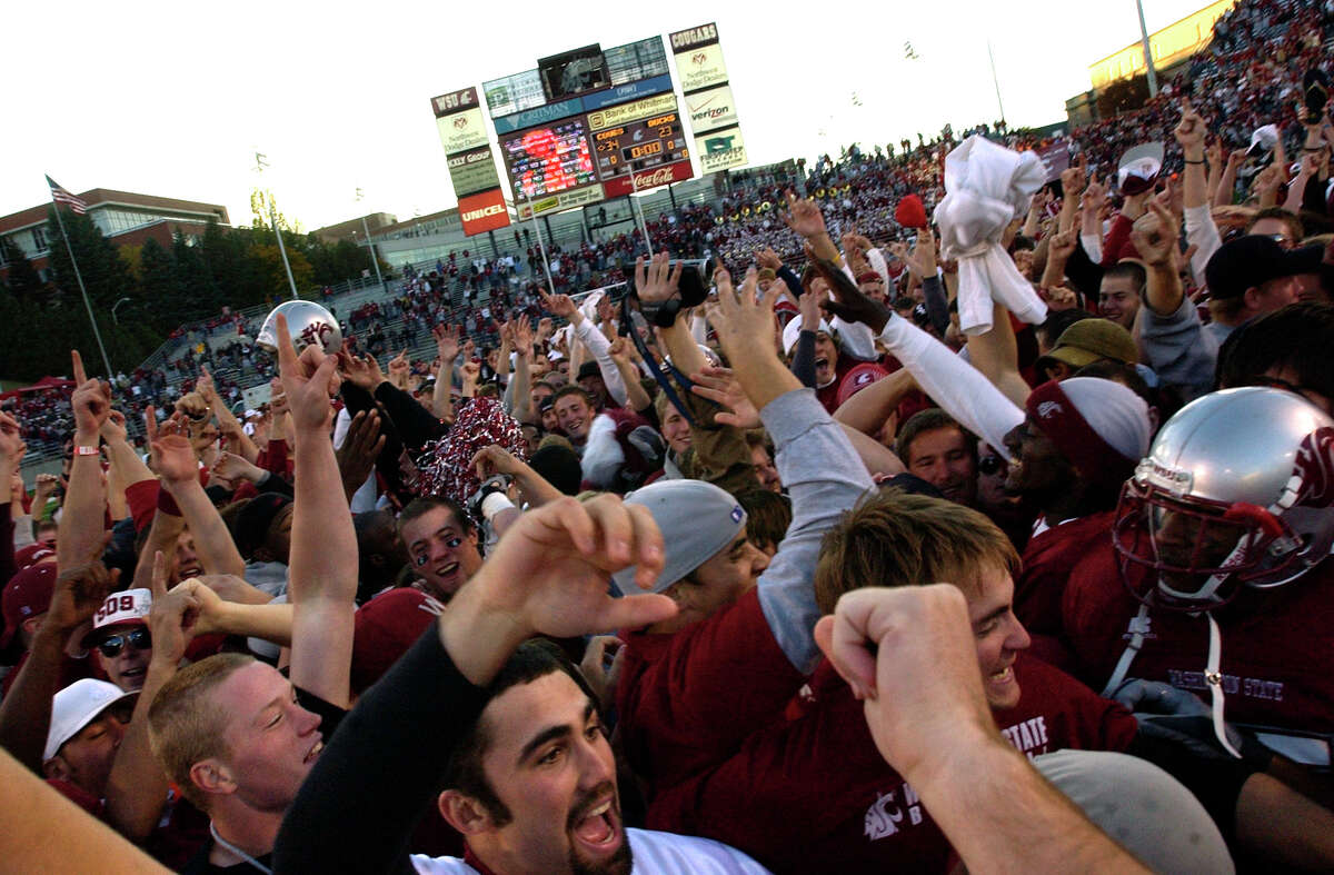 Washington State players and fans fill the field after Washington State upset Oregon 34-23 in Pullman on Oct. 21, 2006.