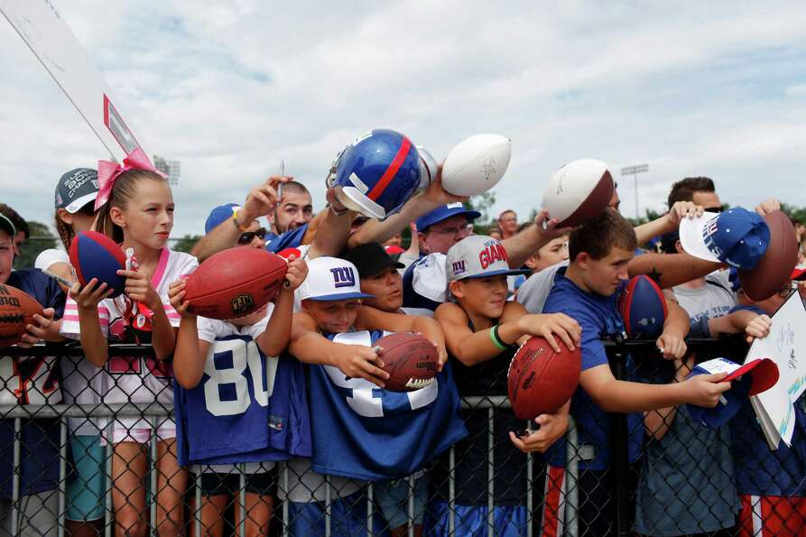 Fans reach out for autographs from New York Giants players at the end of practice during preseason t