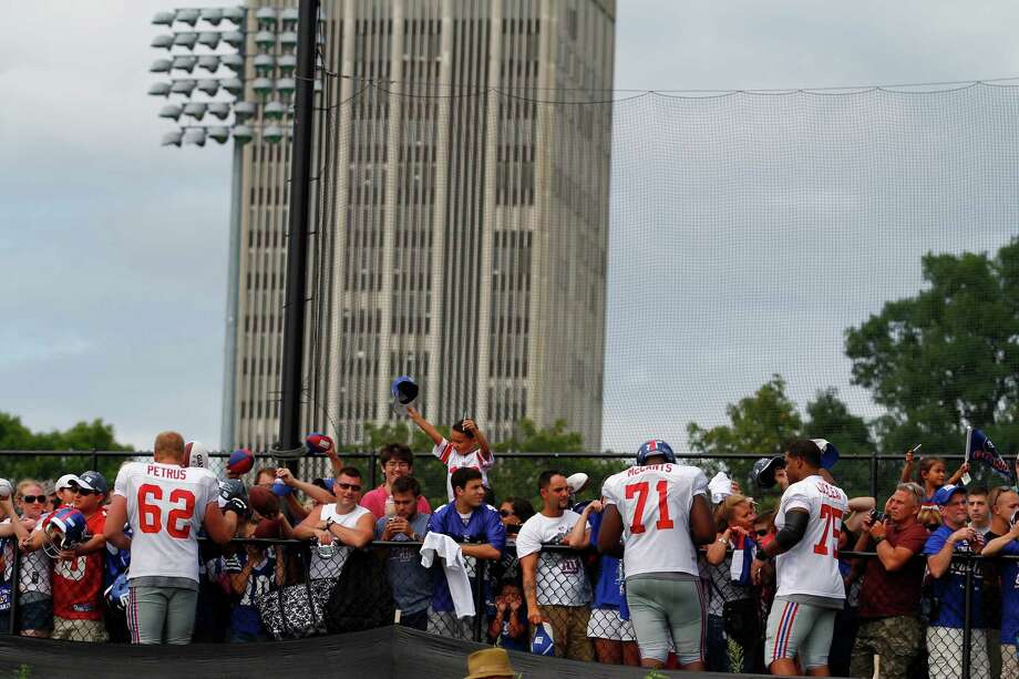 Fans line the fence for autographs from New York Giants players at the end of practice during preseason training camp at UAlbany on Monday Aug. 13, 2012 in Albany, N.Y. (Dan Little/Special to the Times Union) Photo: Dan Little / 00018767D