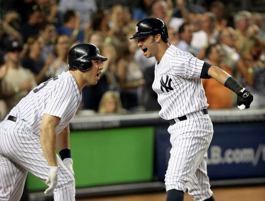 The Yankees' Mark Teixeira is ready to celebrate with Nick Swisher after Swisher's third-inning grand slam. Photo: Seth Wenig / AP