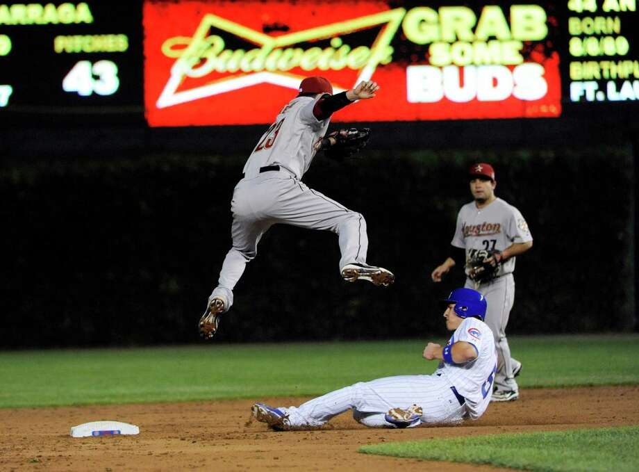 Astros shortstop Tyler Greene goes high to take the throw from catcher Jason Castro as the Cubs' Josh Vitters slides under him for a stolen base in the third inning of Monday night's game. Photo: David Banks / 2012 Getty Images