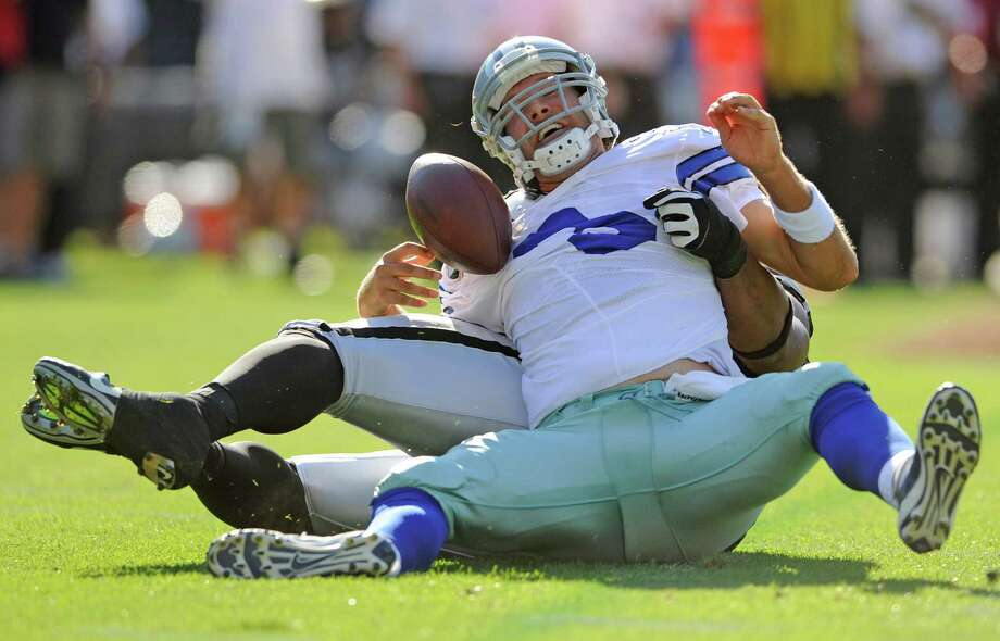 Raiders nose tackle Tommy Kelly sacks the Cowboys' Tony Romo for a 12-yard loss in the first quarter. Photo: JOSE CARLOS FAJARDO / Contra Costa Times