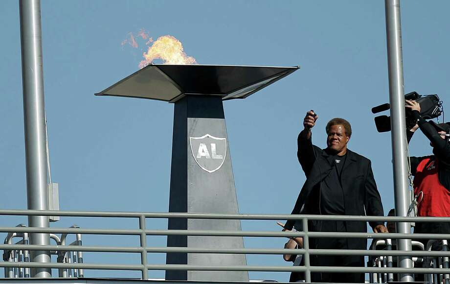 Oakland Raiders general manager Reggie McKenzie lights a flame for former owner Al Davis before an NFL preseason football game against the Dallas Cowboys in Oakland, Calif., Monday, Aug. 13, 2012. (AP Photo/Ben Margot) Photo: Ben Margot, Associated Press / AP