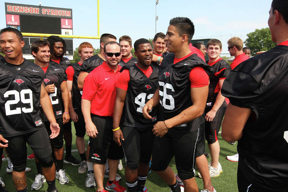 The University of the Incarnate Word Cardinals running backs Dorian Williams, (43), kids around with Alex Torres after a group picture during media day at Benson Stadium, Monday, Aug. 13, 2012. Photo: Jerry Lara, San Antonio Express-News / © 2012 San Antonio Express-News