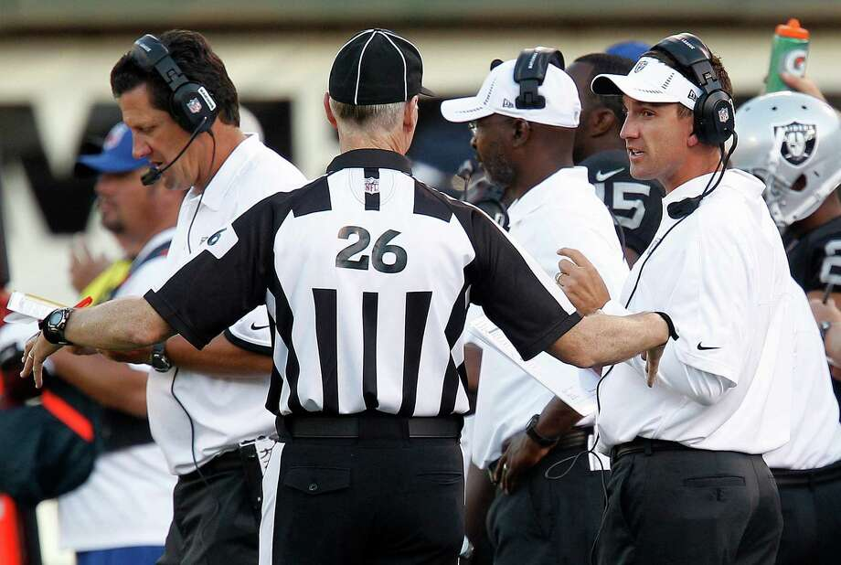 Oakland Raiders head coach Dennis Allen, right, talk with an official during the third quarter of an NFL preseason football game against the Dallas Cowboys in Oakland, Calif., Monday, Aug. 13, 2012. (AP Photo/Tony Avelar) Photo: Tony Avelar, Associated Press / FR155217 AP