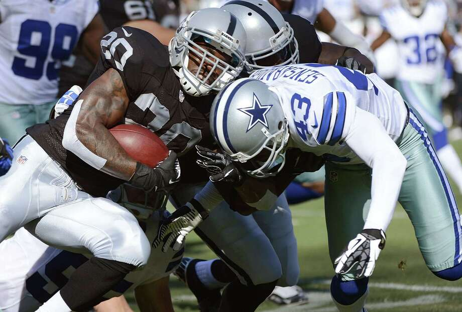 Darren McFadden #20 of the Oakland Raiders gets tackled after a short gain by Gerald Sensabaugh #43 of the Dallas Cowboys in the first quarter of a pre-season NFL football game at O.co Coliseum on August 13, 2012 in Oakland, California. Photo: Thearon W. Henderson, Getty Images / 2012 Getty Images