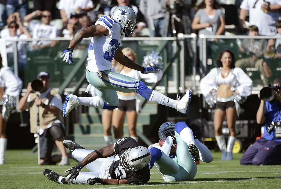 Orlando Scandrick #32 of the Dallas Cowboys leaps over Jacoby Ford #12 of the Oakand Raiders and teammate Gerald Sensabaugh #43 who intercepted the pass in the first quarter of an NFL pre-season football game at O.co Coliseum on August 13, 2012 in Oakland, California. Photo: Thearon W. Henderson, Getty Images / 2012 Getty Images