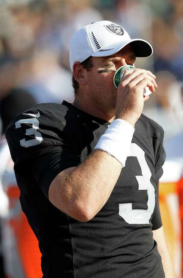 Oakland Raiders quarterback Carson Palmer (3) drinks out of a Gatorade cup during the first half of an NFL preseason football game against the Dallas Cowboys in Oakland, Calif., Monday, Aug. 13, 2012. (AP Photo/Tony Avelar) Photo: Tony Avelar, Associated Press / FR155217 AP