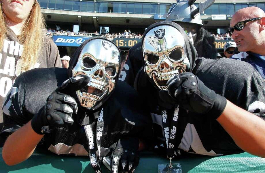 Oakland Raiders fans cheer before an NFL preseason football game between the Oakland Raiders and the Dallas Cowboys in Oakland, Calif., Monday, Aug. 13, 2012. (AP Photo/Tony Avelar) Photo: Tony Avelar, Associated Press / FR155217 AP