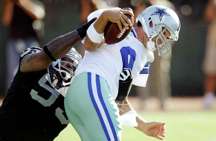 Oakland Raiders defensive tackle Tommy Kelly (93) sacks Dallas Cowboys quarterback Tony Romo (9) during the first quarter of an NFL preseason football game in Oakland, Calif., Monday, Aug. 13, 2012. (AP Photo/Ben Margot) Photo: Ben Margot, Associated Press / AP