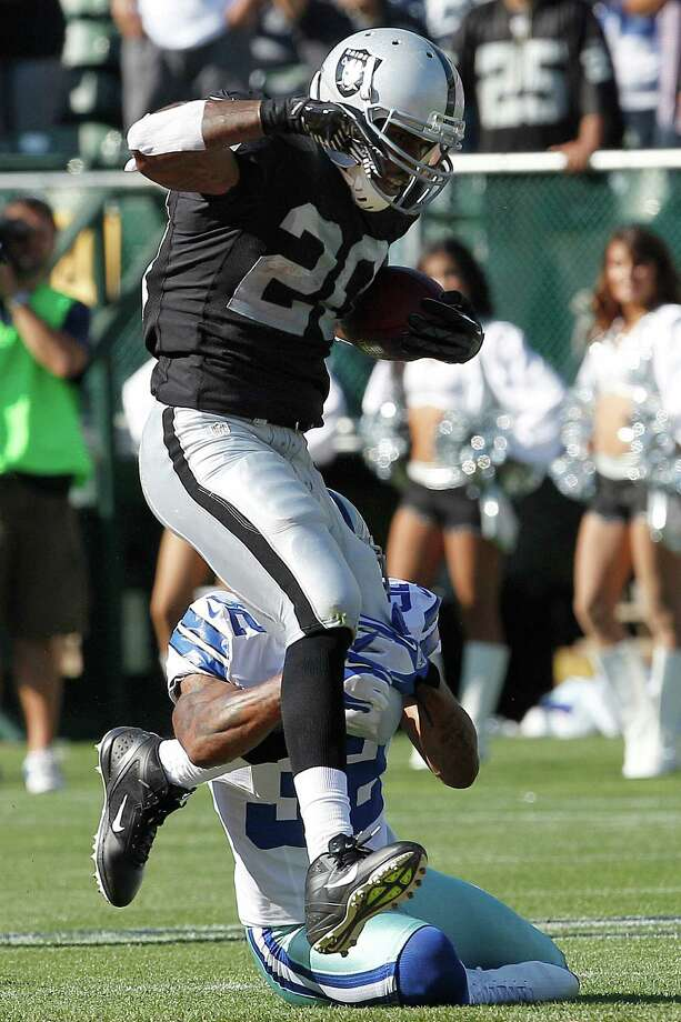 Oakland Raiders running back Darren McFadden (20) rushes against Dallas Cowboys defensive back Orlando Scandrick (32) during the first quarter of an NFL preseason football game in Oakland, Calif., Monday, Aug. 13, 2012. (AP Photo/Tony Avelar) Photo: Tony Avelar, Associated Press / FR155217 AP