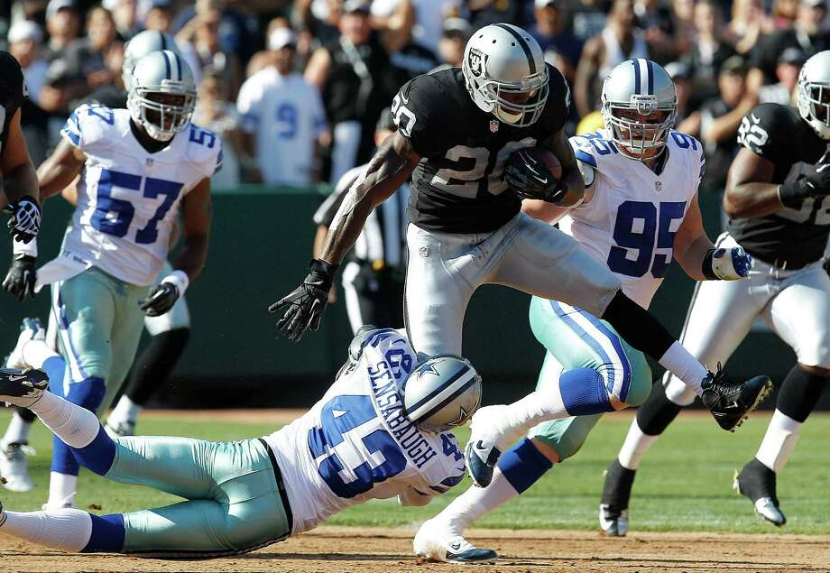 Dallas Cowboys defensive back Gerald Sensabaugh (43) tackles running back Darren McFadden (20) during the first quarter of an NFL preseason football game in Oakland, Calif., Monday, Aug. 13, 2012. (AP Photo/Tony Avelar) Photo: Tony Avelar, Associated Press / FR155217 AP