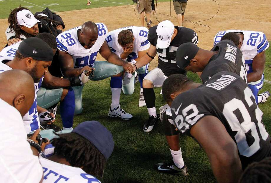 Dallas Cowboys and Oakland Raiders players kneel in prayer after an NFL preseason football game in Oakland, Calif., Monday, Aug. 13, 2012. (AP Photo/Tony Avelar) Photo: Tony Avelar, Associated Press / FR155217 AP