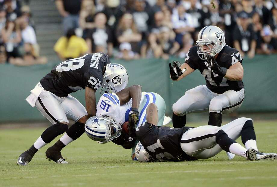 Tim Benford #16 of the Dallas Cowboys gets tackled by Terrail Lambert #31 and Brandon Underwood #28 of the Oakland Raiders in the third quarter of an NFL pre-season football game at O.co Coliseum on August 13, 2012 in Oakland, California. Photo: Thearon W. Henderson, Getty Images / 2012 Getty Images