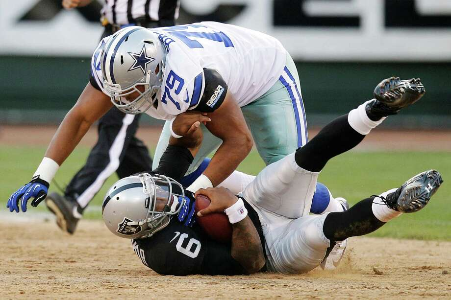 Dallas Cowboys defensive end Ben Bass (79) tackles Oakland Raiders quarterback Terrelle Pryor (6) during the second half of an NFL preseason football game in Oakland, Calif., Monday, Aug. 13, 2012. (AP Photo/Ben Margot) Photo: Ben Margot, Associated Press / AP