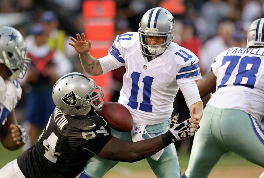 Oakland Raiders defensive tackle Dominique Hamilton (64) tackles Dallas Cowboys quarterback Rudy Carpenter (11) causing a fumble, which Dallas recovered, during the fourth quarter of an NFL preseason football game in Oakland, Calif., Monday, Aug. 13, 2012. (AP Photo/Ben Margot) Photo: Ben Margot, Associated Press / AP