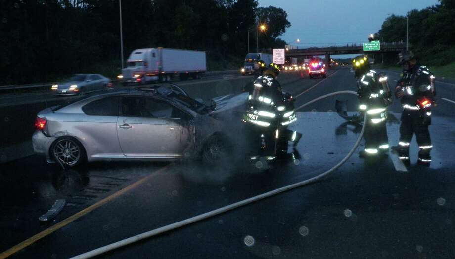 Westport firefighters extinguish a fire that erupted in this car after it struck the Interstate 95 median between northbound Exits 17 and 18 Monday night. Photo: Westport Fire Department / Westport News contributed