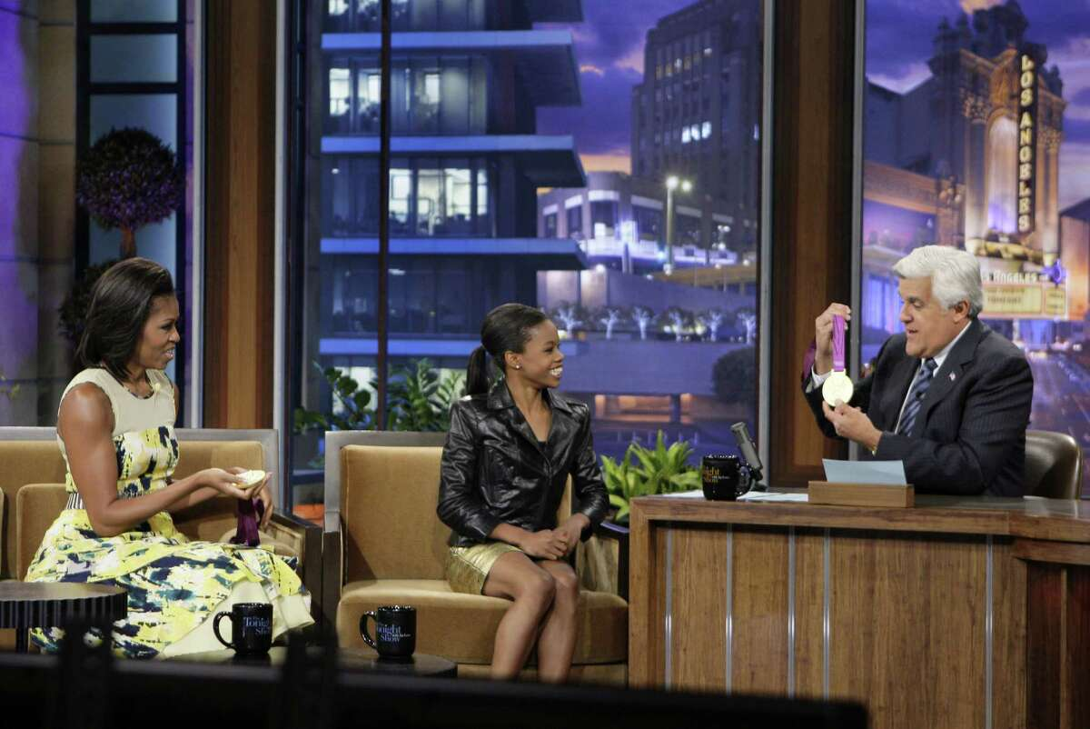 """This Monday, Aug. 13, 2012 photo released by NBC shows first lady Michelle Obama, left, olympic gold medalist Gabby Douglas and host Jay Leno during a taping of """"The Tonight Show with Jay Leno,"""" in Burbank, Calif. (AP Photo/NBC, Margaret Norton)"""