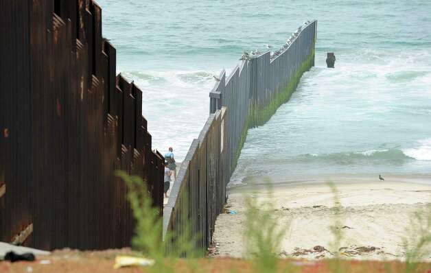 "A couple of people approach the wall on Tijuana-side of the Border Field State Park fence, which separates the cities of San Diego and Tijuana at the US-Mexico border going three hundred feet into the Pacific Ocean, on August 12, 2012 in San Diego, California, at the launch of ""caravan for peace"" across the United States, a month-long campaign to protest the two countries' brutal drug war.  The caravan departed from Tijuana with about 250 participants and is due to end in Washington on September 10.      AFP PHOTO / Frederic J. BROWN        (Photo credit should read FREDERIC J. BROWN/AFP/GettyImages) Photo: Getty Images"