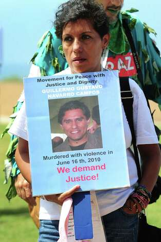 "A woman displays a photograph of a deceased loved one at Border Field State Park, which separates the cities of San Diego and Tijuana at the US-Mexico border on August 12, 2012 in San Diego, California, at the launch of ""caravan for peace"" across the United States, a month-long campaign to protest the two countries' brutal drug war.  The caravan departed from Tijuana with about 250 participants and is due to end in Washington on September 10.    AFP PHOTO / Frederic J. BROWN        (Photo credit should read FREDERIC J. BROWN/AFP/GettyImages) Photo: Getty Images"