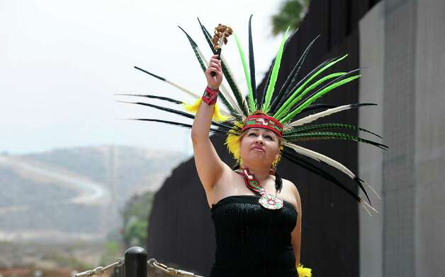 "An Aztec dancer performs at the Border Field State Park fence, which separates the cities of San Diego and Tijuana at the US-Mexico border on August 12, 2012 in San Diego, California, at the launch of ""caravan for peace"" across the United States, a month-long campaign to protest the two countries' brutal drug war.  The caravan departed from Tijuana with about 250 participants and is due to end in Washington on September 10.     AFP PHOTO / Frederic J. BROWN        (Photo credit should read FREDERIC J. BROWN/AFP/GettyImages) Photo: Getty Images"
