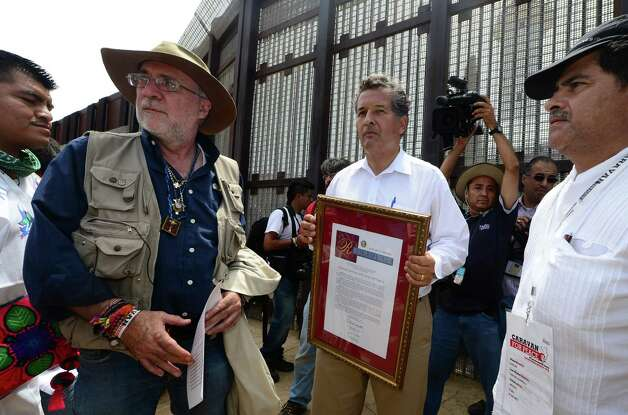 "Mexican peace activist Javier Sicilia (2/L) and California Senator Juan Vargas (C) arrive at the US-Mexico border separating the cities of San Diego and Tijuana at Border Field State Park on August 12, 2012 in San Diego, California, to launch ""caravan for peace"" across the United States in a month-long campaign to protest the two countries' brutal drug war.  The caravan departed from Tijuana with about 250 participants and is due to end in Washington on September 10.    AFP PHOTO / Frederic J. BROWN        (Photo credit should read FREDERIC J. BROWN/AFP/GettyImages) Photo: Getty Images"