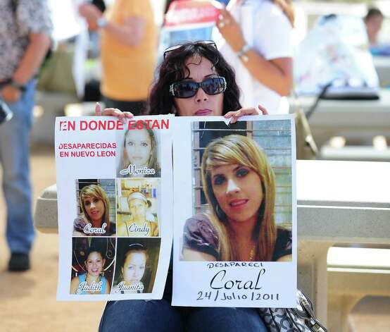 "A woman displays photographs of deceased or missing loved ones as people gather at Border Field State Park, which separates the cities of San Diego and Tijuana, at the US-Mexico border on August 12, 2012 in San Diego, California, to launch ""caravan for peace"" across the United States in a month-long campaign to protest the two countries' brutal drug war.  The caravan departed from Tijuana with about 250 participants and is due to end in Washington on September 10.      AFP PHOTO / Frederic J. BROWN        (Photo credit should read FREDERIC J. BROWN/AFP/GettyImages) Photo: Getty Images"