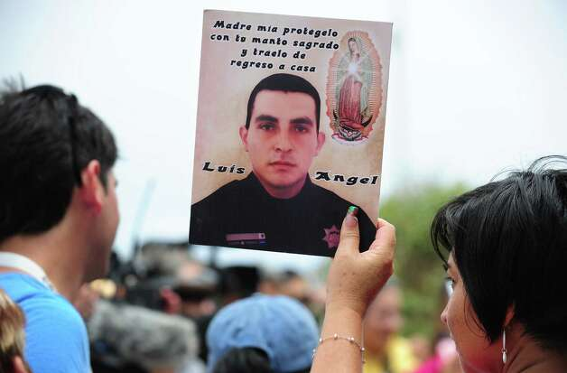"A woman holds a portrait of a deceased or missing loved one as people gather at Border Field State Park, which separates the cities of San Diego and Tijuana, at the US-Mexico border on August 12, 2012 in San Diego, California, to launch ""caravan for peace"" across the United States in a month-long campaign to protest the two countries' brutal drug war.  The caravan departed from Tijuana with about 250 participants and is due to end in Washington on September 10.    AFP PHOTO / Frederic J. BROWN        (Photo credit should read FREDERIC J. BROWN/AFP/GettyImages) Photo: Getty Images"