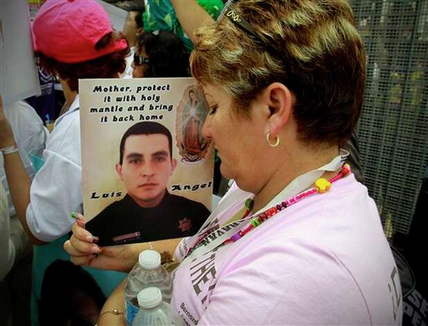 Araceli Rodriguez, closes her eyes as she holds a photo of her son, Luis Angel Leon, a federal police officer in Mexico City, killed in 2009, a casualty of the drug war, during the Caravan for Peace rally at the border fence in Friendship Park at Border Field State Park, Sunday, Aug. 12, 2012. The Caravan for Peace will travel across America and arrive in Washington, D.C., September 12, and is calling attention to the drug violence, immigration, and other issue affecting both Mexico and the United States. (AP Photo/UT San Diego, Howard Lipin) NO SALES, ONLINE OUT, NO ARCHIVING, SAN DIEGO COUNTY OUT, TV OUT, MAGS OUT, NO FORNS.  TABLOIDS OUT. COMMERCIAL INTERNET USE OUT Photo: Howard Lipin, Associated Press / UT San Diego