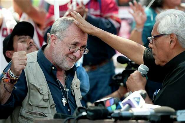 Poet Javier Sicilia, left, is blessed by Father Richard Estrada, right, during an arrival ceremony held by the Caravan for Peace, in Los Angeles on Monday, Aug. 13, 2012. The caravan is traveling across the country to  promote the alliance of the US and Mexico to fight the drug war. (AP Photo/Grant Hindsley) Photo: Grant Hindsley, Associated Press / AP