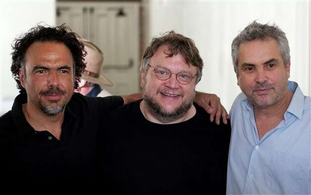 Directors Alejandro Gonz�lez I��rritu, left, Guillermo del Toro, middle, and Alfonso Cuar�n, right, pose for photos before a press conference held by the Caravan for Peace, in Los Angeles on Monday, Aug. 13, 2012. The caravan is traveling across the country to  promote the alliance of the US and Mexico to fight the drug war. (AP Photo/Grant Hindsley) Photo: Grant Hindsley, Associated Press / AP