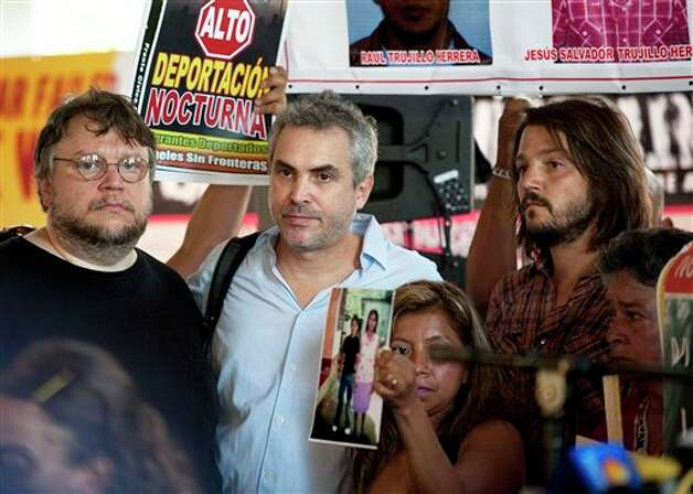 Guillermo del Toro, left, Alfonso Cuar�n, middle, and actor Diego Luna, right, stand on stage during a press conference held by the Caravan for Peace, in Los Angeles on Monday, Aug. 13, 2012. The caravan is traveling across the country to  promote the alliance of the US and Mexico to fight the drug war. (AP Photo/Grant Hindsley) Photo: Grant Hindsley, Associated Press / AP