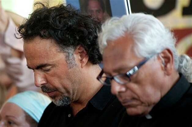 Director Alejandro Gonz�lez I��rritu, left, and Father Richard Estrada, right, listen to the stories of lost loved ones in the Mexican drug war during a news conference held by the Caravan for Peace in Los Angeles Monday, Aug. 13, 2012. The caravan is traveling across the country to  promote the alliance of the U.S. and Mexico to fight the drug war. (AP Photo/Grant Hindsley) Photo: Grant Hindsley, Associated Press / AP2012