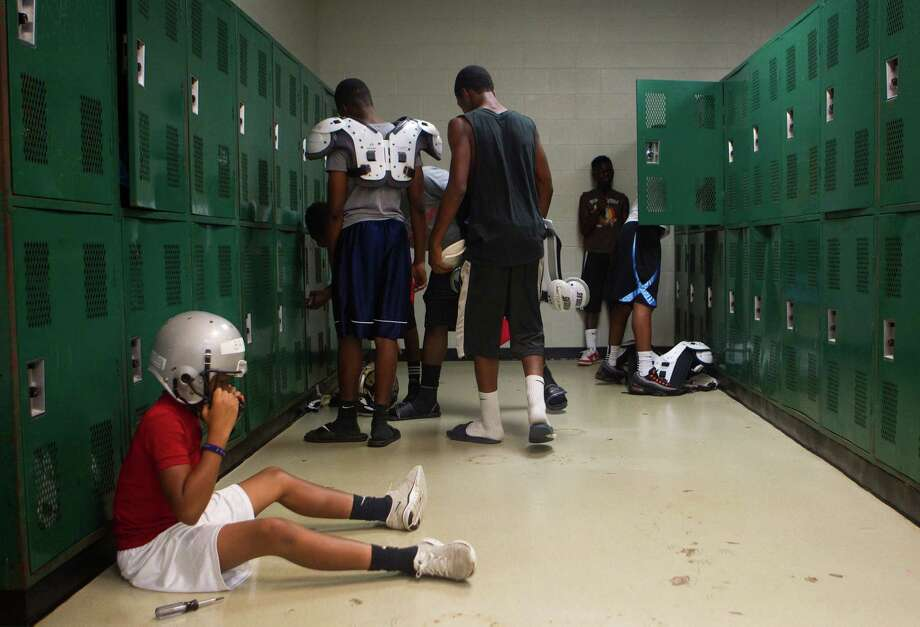 Hightower High School freshmen Devin Bracy puts on his helmet after getting football equipment at Hightower High School Monday, Aug. 13, 2012, in Missouri City. Photo: Cody Duty, Houston Chronicle / © 2011 Houston Chronicle