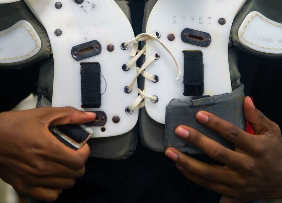 A Hightower High School football player tries on pads at Hightower High School Monday, Aug. 13, 2012, in Missouri City. Photo: Cody Duty, Houston Chronicle / © 2011 Houston Chronicle