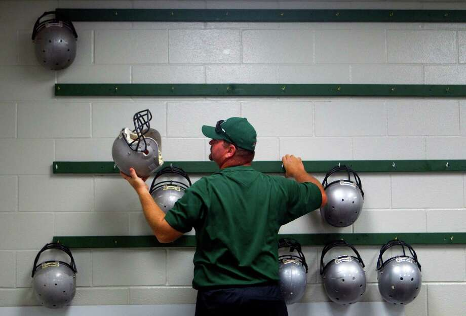 Hightower High School football coach Steven Vlasek grabs a helmet for a player Hightower High School Monday, Aug. 13, 2012, in Missouri City. Photo: Cody Duty, Houston Chronicle / © 2011 Houston Chronicle