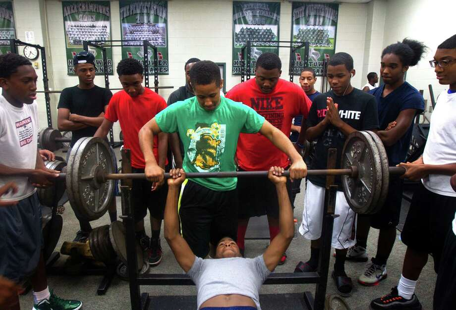 Hightower High School freshmen Fred gibson is helped by Cameron Young as he tries to bench press 225 pounds at Hightower High School Monday, Aug. 13, 2012, in Missouri City. Photo: Cody Duty, Houston Chronicle / © 2011 Houston Chronicle