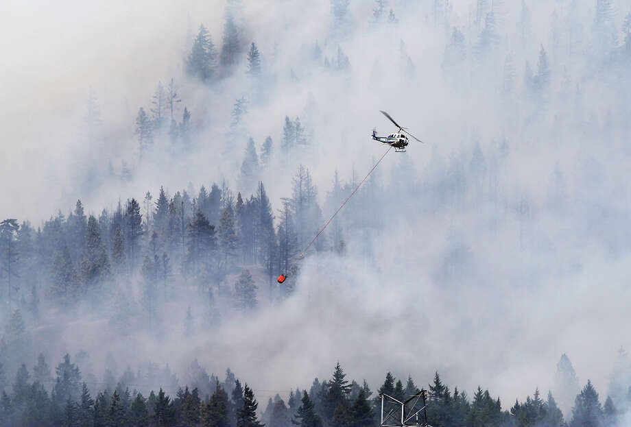 A firefighting helicopter, operated by the Washington  Department of Natural Resources, battles the Taylor Bridge Fire east of Cle Elum on Monday. (AP Photo/Daily Record/Brian Myrick ) Photo: Associated Press