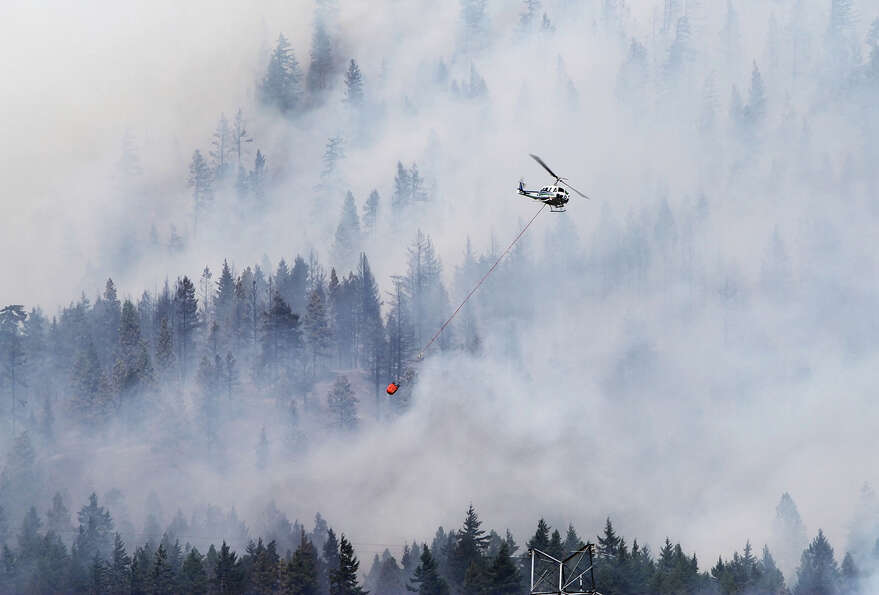 A firefighting helicopter, operated by the Washington  Department of Natural Resources, battles the