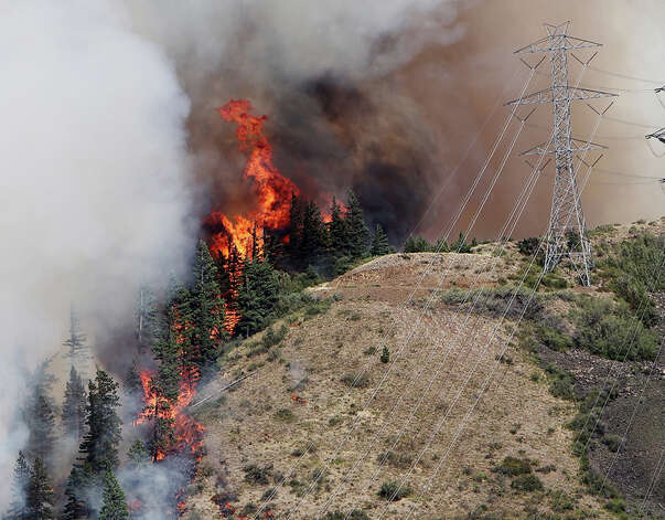 Flames from the Taylor Bridge Fire climb the side of Lookout Mountain east of Cle Elum on Monday.. (AP Photo/Daily Record/Brian Myrick ) Photo: Associated Press