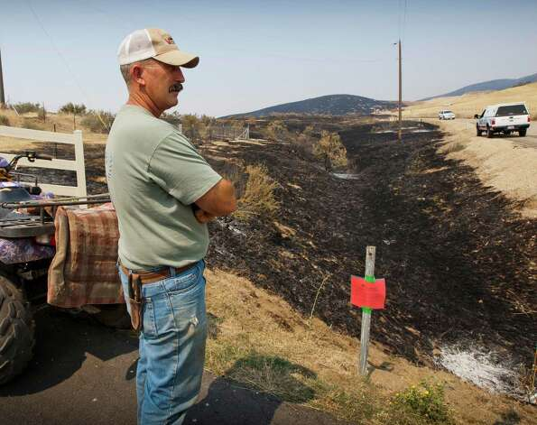 Cattle rancher Bryan Brodin looks at the 419 acres that scorched the foothills north of Cartwright Road near Hidden Springs, Idaho relieved that most of his cattle were higher up in the hills before fire crews contained the blaze Monday2. The Ourada Ranch Fire  threatened several homes and ranches but firefighters and local farmers prevented the fire's spread with plows, fire lines and an air attack dropping water on hot spots. (AP Photo/The Idaho Statesman, Darin Oswald) Photo: Associated Press
