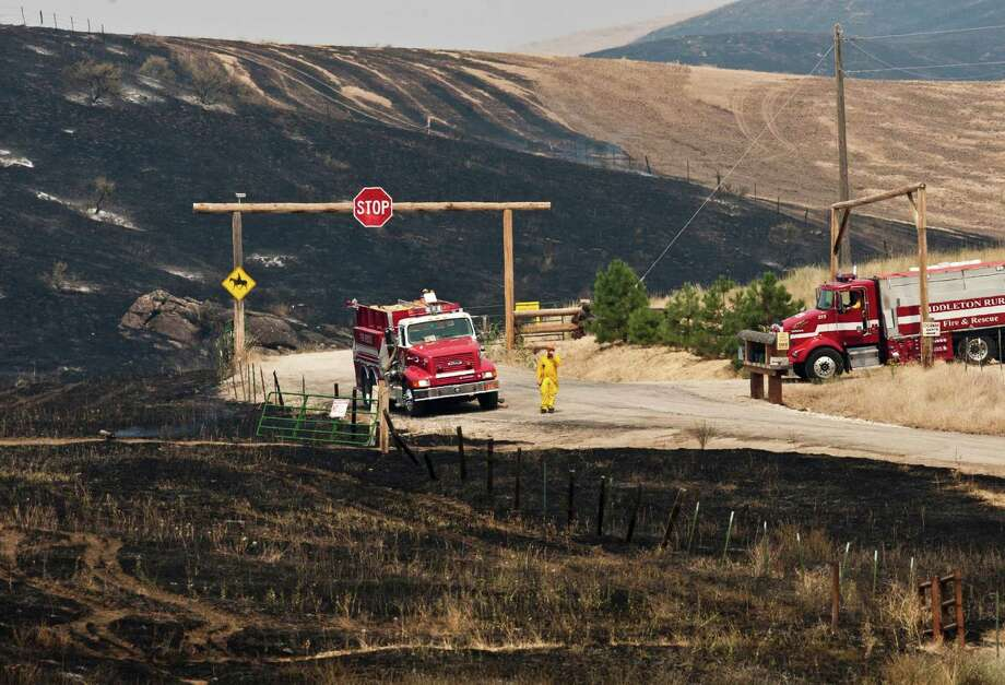 Fire crews from multiple agencies contain the Ourada Ranch Fire in the foothills northeast of Hidden Springs above Cartwright Road in Boise, Idaho, on Monday.. The fire burned 419 acres and threatened several homes and ranches. (AP Photo/The Idaho Statesman, Darin Oswald) Photo: Associated Press